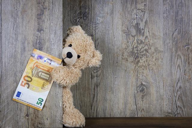 壁の向こうから、かわいい熊のぬいぐるみがお札をもって覗いている。