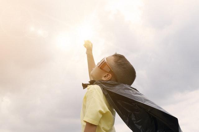 空に向かってこぶしを突き上げるスーパーマン少年