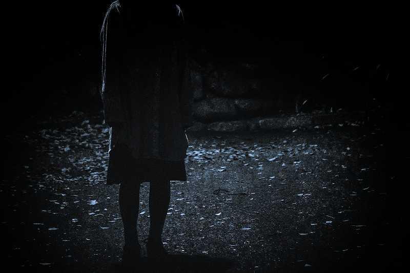 暗闇にたたずむ女性