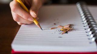 鉛筆でノートに書きこむ手のアップ